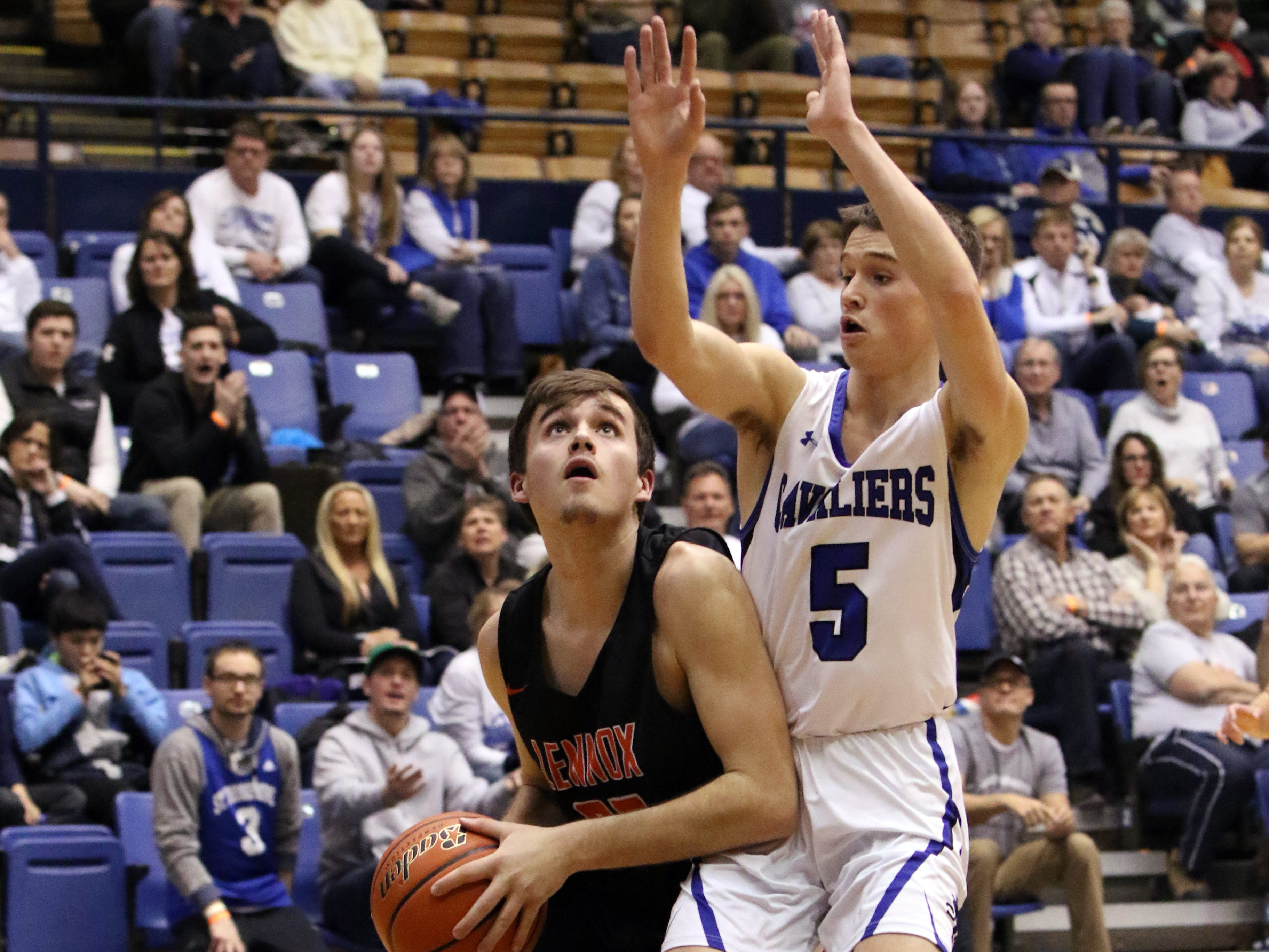 Kaleb Johnson of Lennox eyes the basket as Michael Gylten of St Thomas More defends during Thursday's game at the Arena.