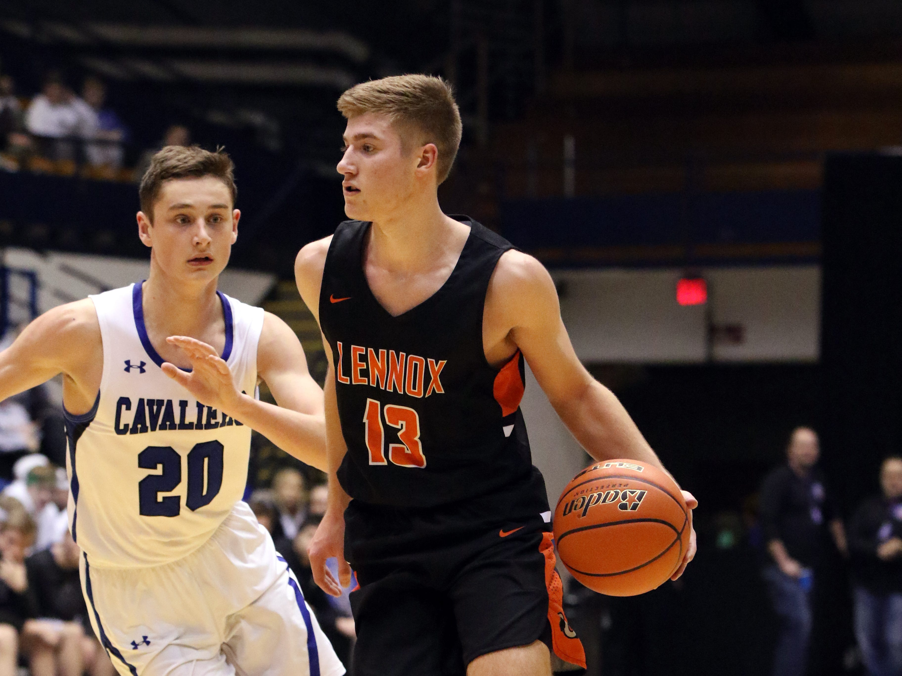 Quincy Ihnen of Lennox dribbles away from the defense by Connor Hollenbeck of St Thomas More during Thursday night's game at the Arena in Sioux Falls.