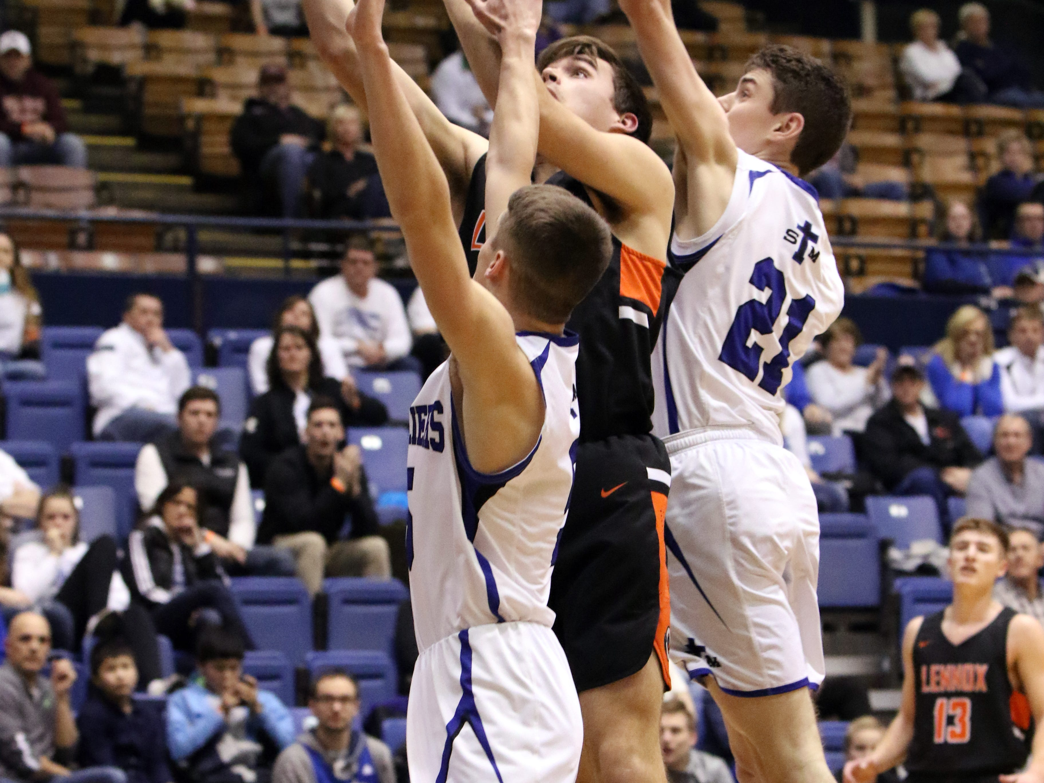 Kaleb Johnson of Lennox puts up a shot between several St Thomas More players during Thursday night's game at the Arena in Sioux Falls.