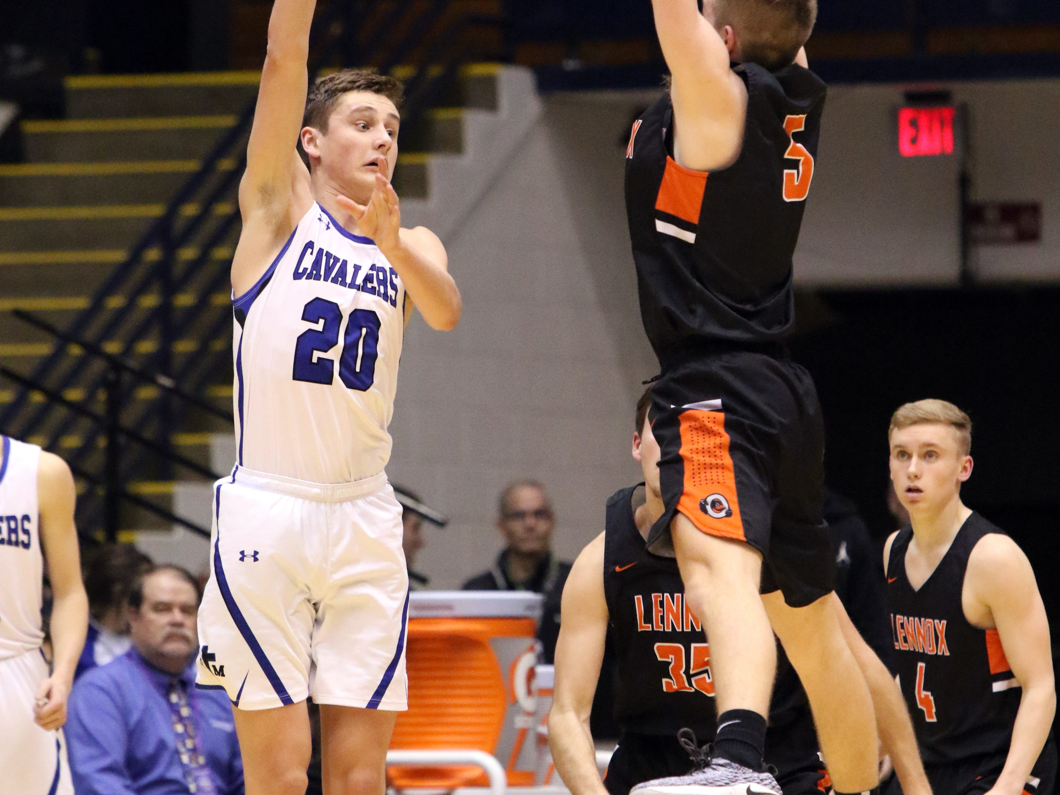 Josh Arlt of Lennox goes up to block the pass by Connor Hollenbeck of St Thomas More during Thursday night's game at the Arena in Sioux Falls.