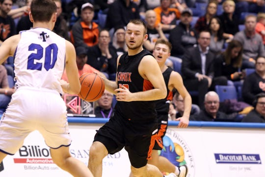 Will Daugherty of Lennox brings the ball up as Connor Hollenbeck of St Thomas More defends during Thursday night's game at the Arena in Sioux Falls.
