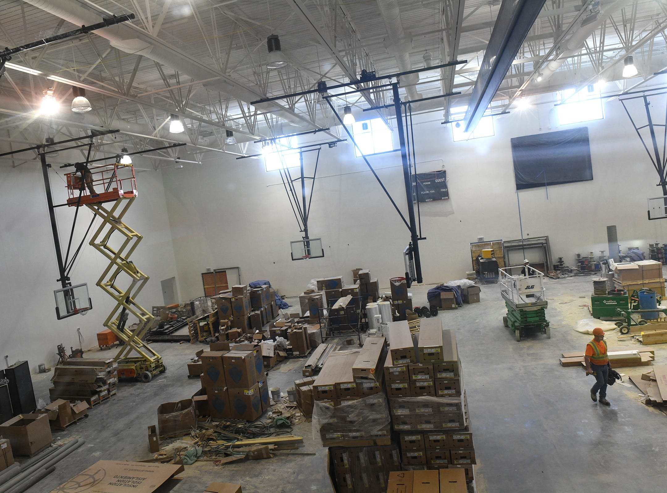Workers complete tasks in the gymnasium at the new Tech High School building under construction Friday, March 15, in St. Cloud.