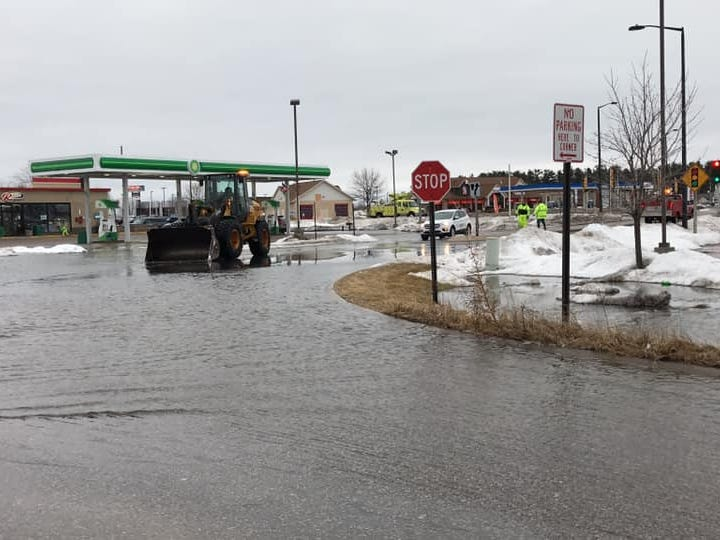 Crews work to remove flood water from the roads near the R Store in Plover on Friday, March 15, 2019.