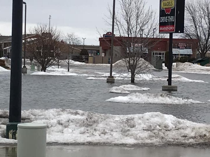 Water stands in the roads and parking lots near R Store and the former Big Apple Bagels in Plover on Friday, March 15, 2019..