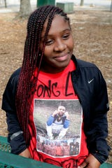 "Derreecia Williams, 16, proudly shows off a ""long live Cobi"" shirt in honor of Cobi Mathis, 17, who was shot and killed in broad daylight in the parking lot of an Old Bainbridge Road daycare Monday, Feb. 25, 2019."