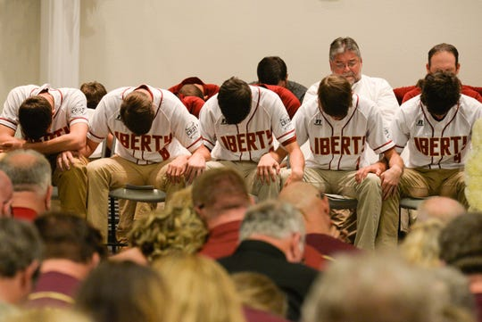 The Liberty County High School baseball team bows their heads in prayer during a memorial service held for Corey and Shana Crum at the Veterans Memorial Civic Center in Bristol, Fla. Friday, March 15, 2019. The couple died after being electrocuted at the Liberty County High School baseball field Sunday, March 10, 2019.