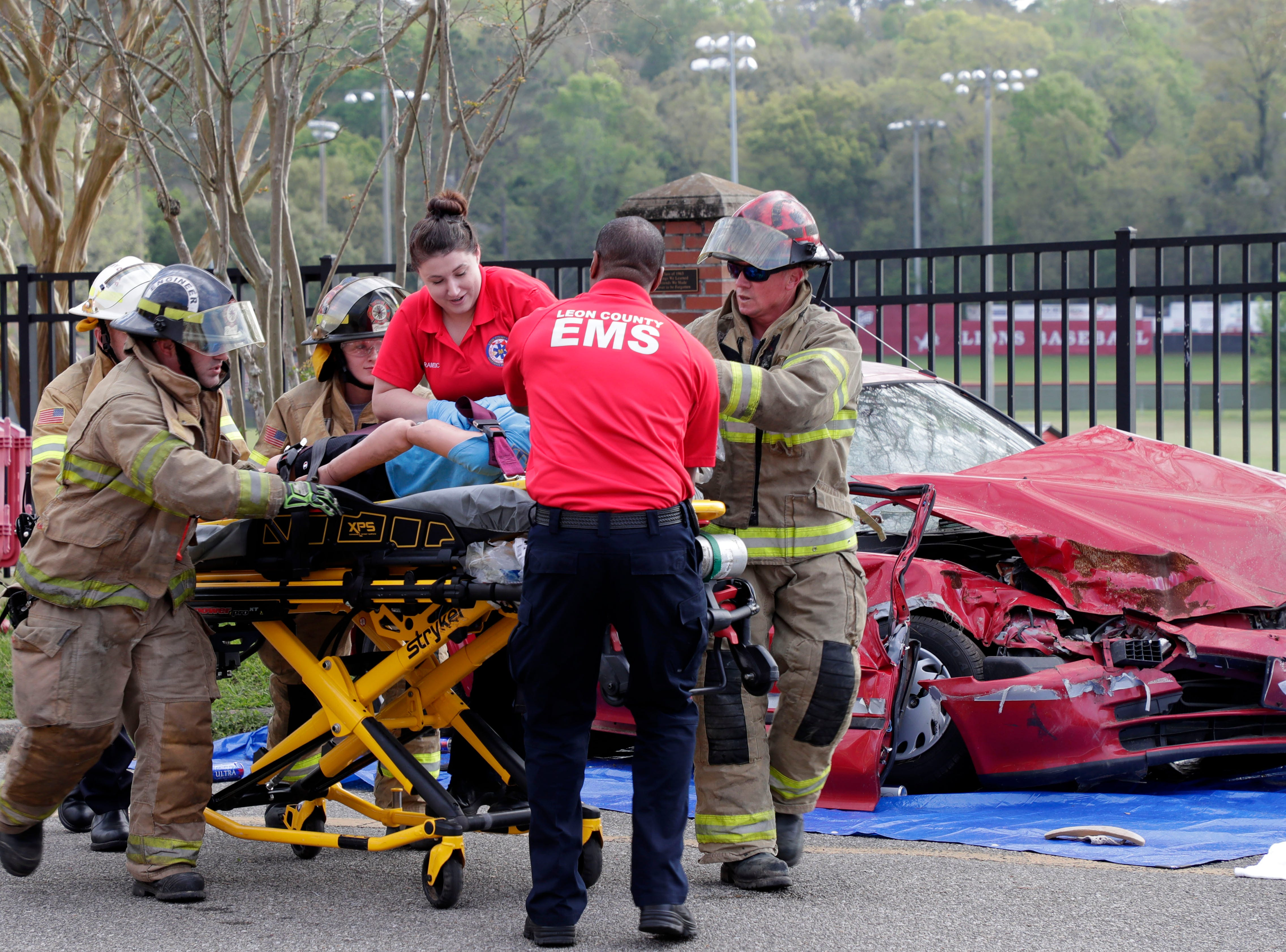 Leon County firefighters and paramedics rush a dummy to an ambulance. Leon High School partners with the county safety officials to give a simulation on the consequences of drunk driving before the students leave for spring break Friday, March 15, 2019.