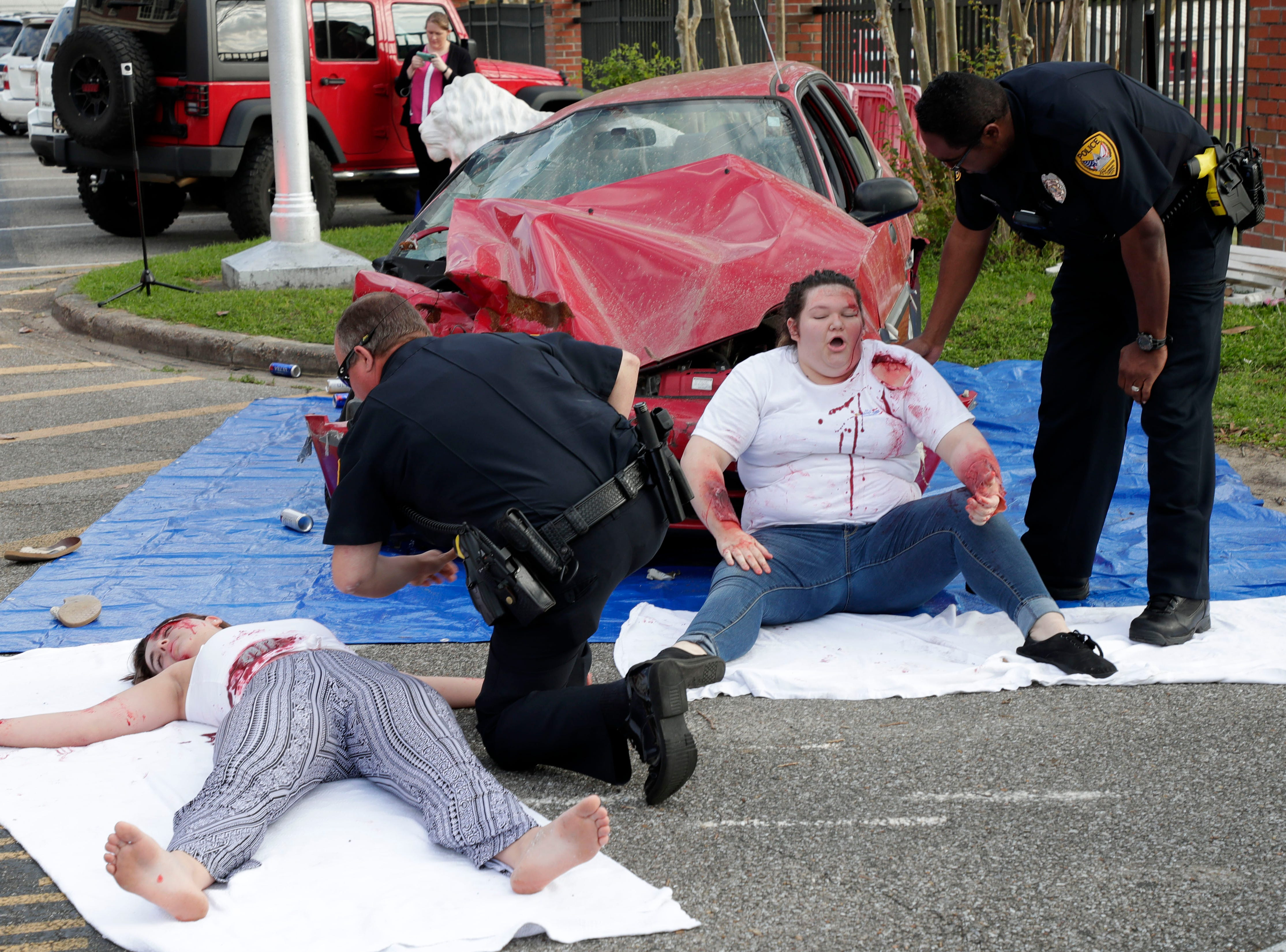 Police offers check on Christina Huettel, left, and her friend Caitlyn Burke as the teens portray people involved in a drinking and driving accident. Leon High School partners with the county safety officials to give a simulation on the consequences of drunk driving before the students leave for spring break Friday, March 15, 2019.