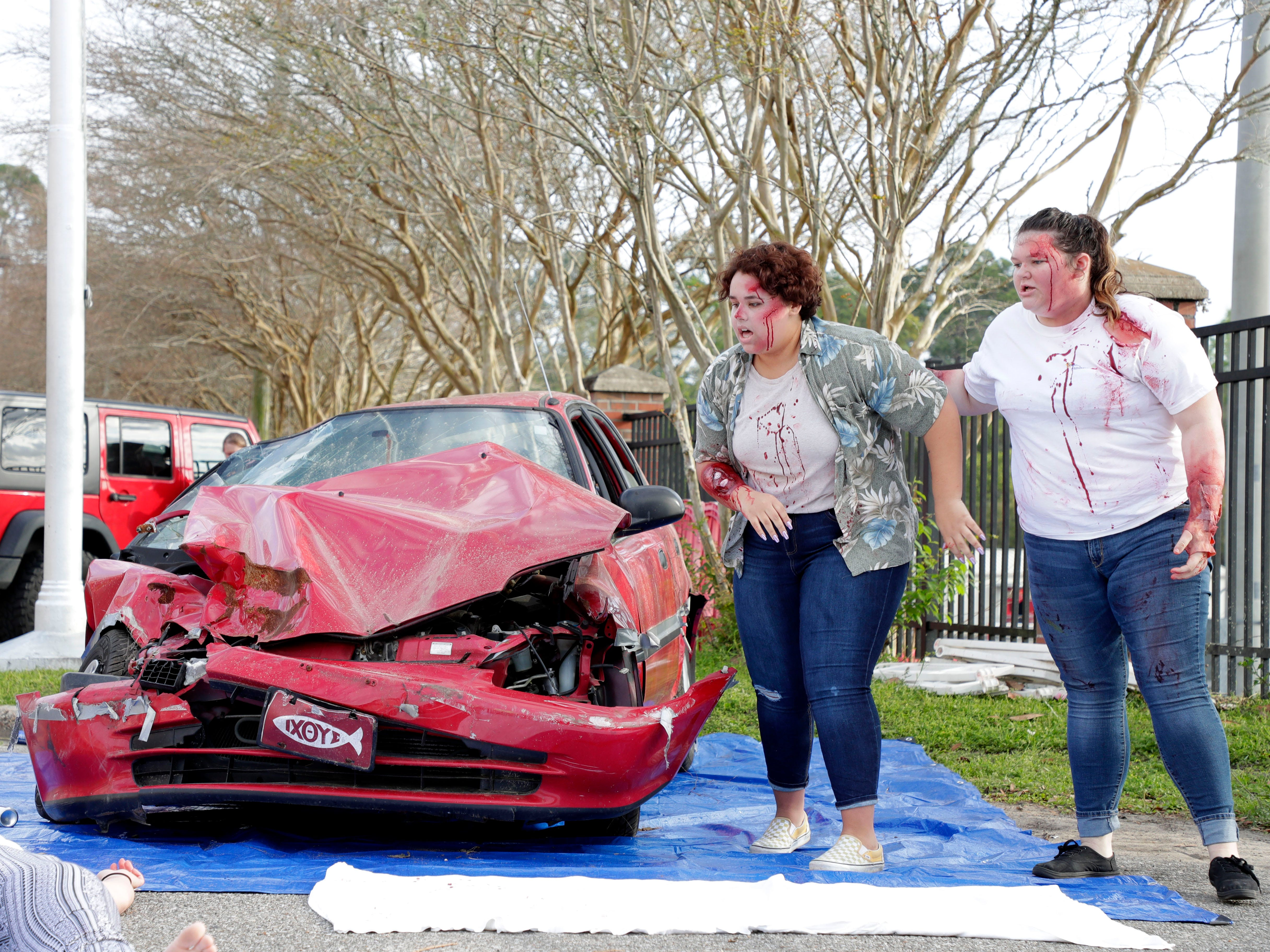 Mia Ford-Green, left, and Caitlyn Burke run to check on their friend as they portray teens involved in a drinking and driving accident. Leon High School partners with the county safety officials to give a simulation on the consequences of drunk driving before the students leave for spring break Friday, March 15, 2019.