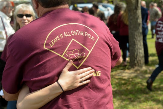 Following a memorial service for Corey and Shana Crum, hundreds gathered in front of the Veterans Memorial Civic Center to hug and share their grief, many wearing garnet shirts dedicated to the couple who died Sunday after being electrocuted at the Liberty County High School baseball field.