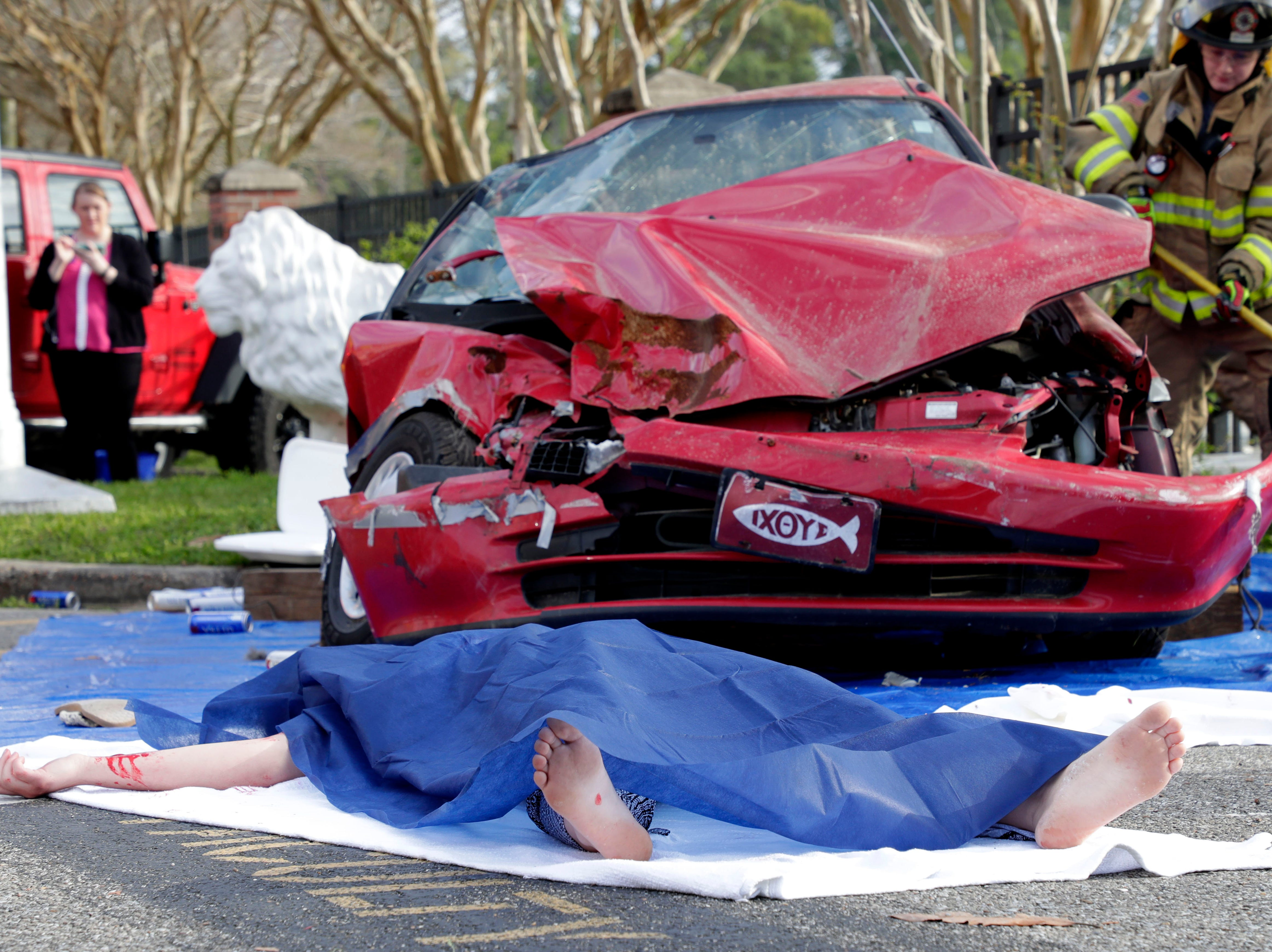 Christina Huettel lays in front of a car severely damaged from a drinking and driving accident. Leon High School partners with the county safety officials to give a simulation on the consequences of drunk driving before the students leave for spring break Friday, March 15, 2019.