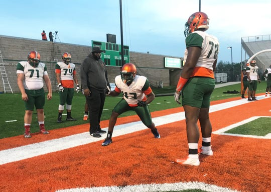 FAMU offensive line coach Alex Jackson works closely with Marquise Sailor on his first step during spring practice on March 12, 2019.