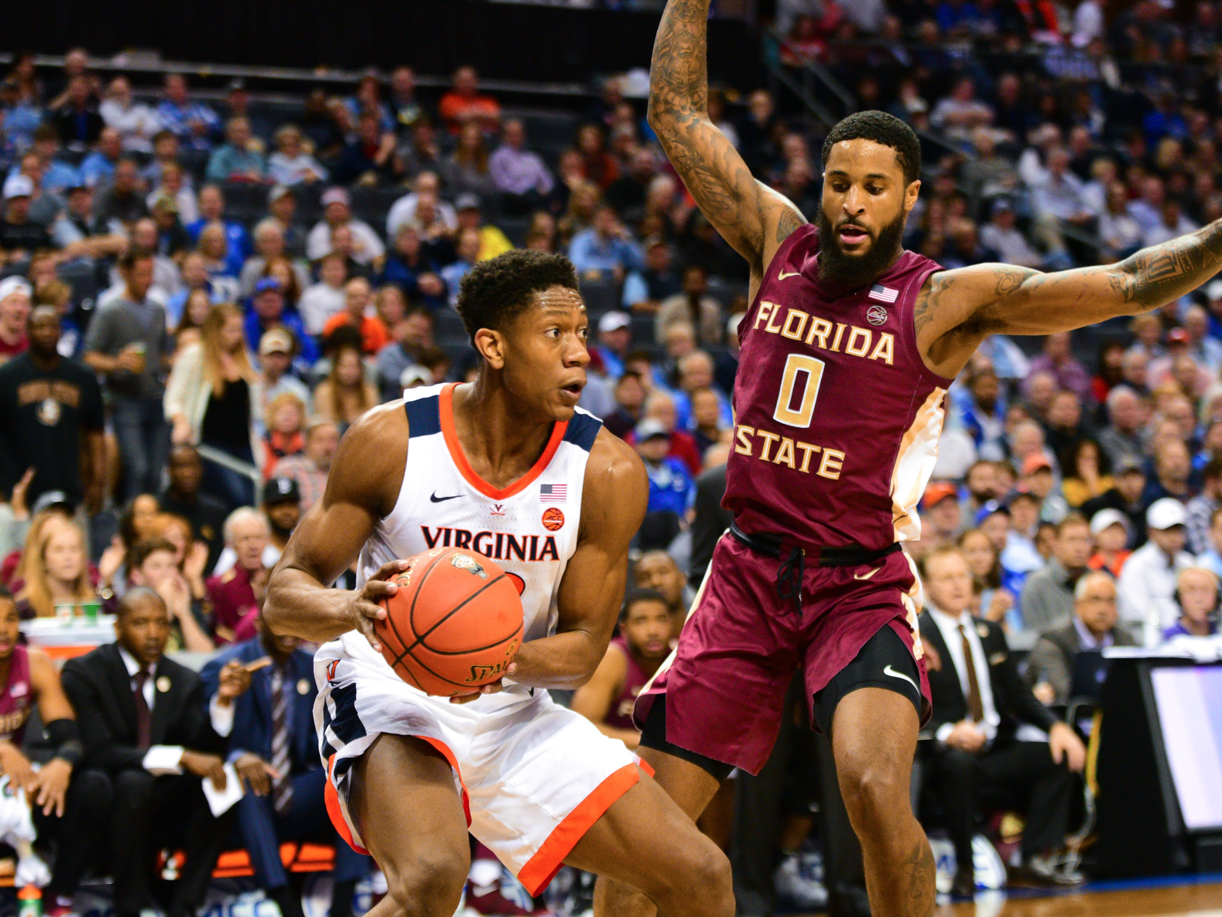 Florida State redshirt senior guard Phil Cofer, right, blocks Virginia redshirt sophomore guard De'andre Hunter  during the first half of the ACC Tournament Semifinals at the Spectrum Center in Charlotte on Friday.