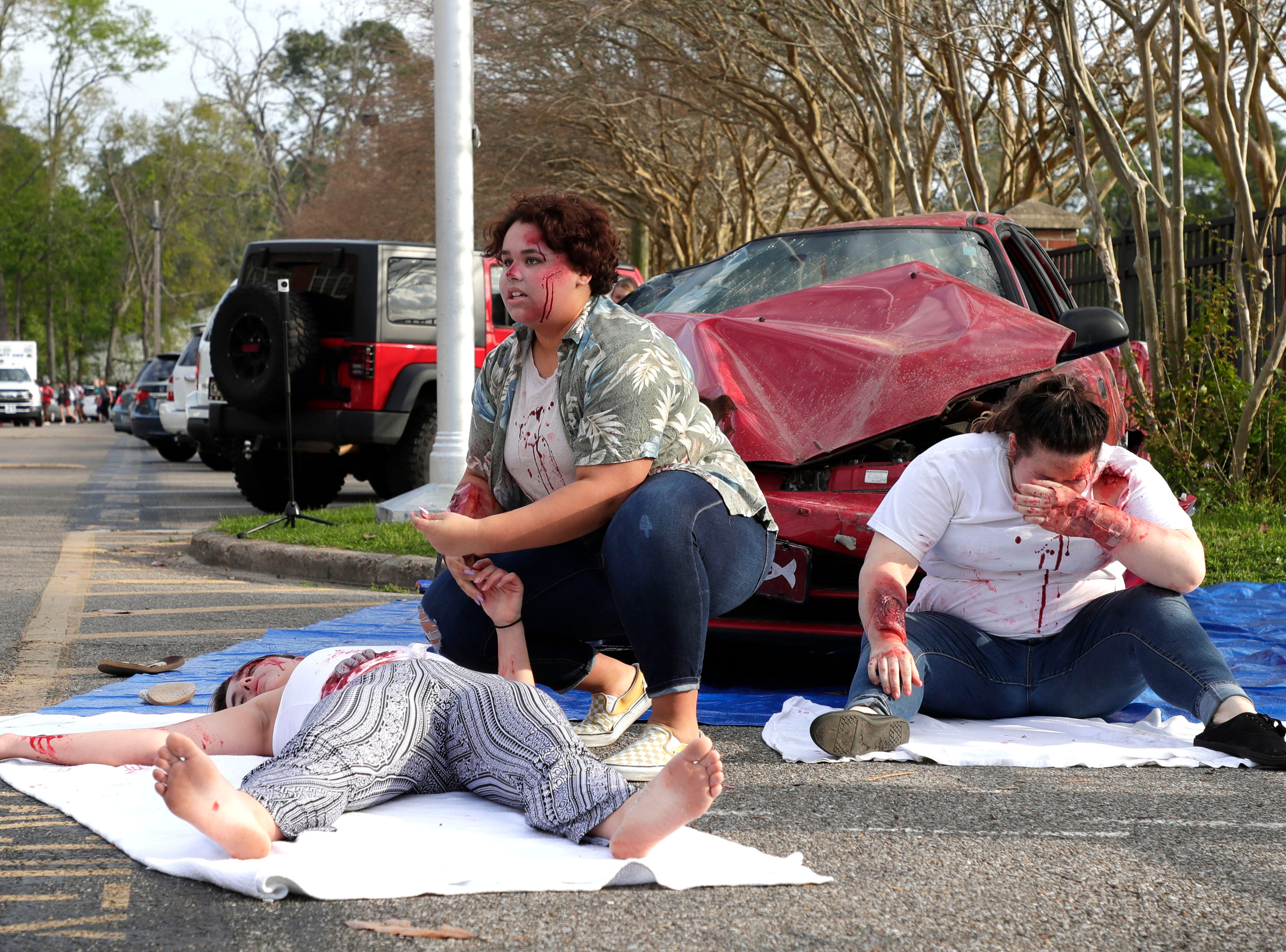 Mia Ford-Green, center, checks Christina Huettel's, left, pulse while Caitlyn Burke hyperventilates. The three teens portray teens involved in a drinking and driving accident. Leon High School partners with the county safety officials to give a simulation on the consequences of drunk driving before the students leave for spring break Friday, March 15, 2019.