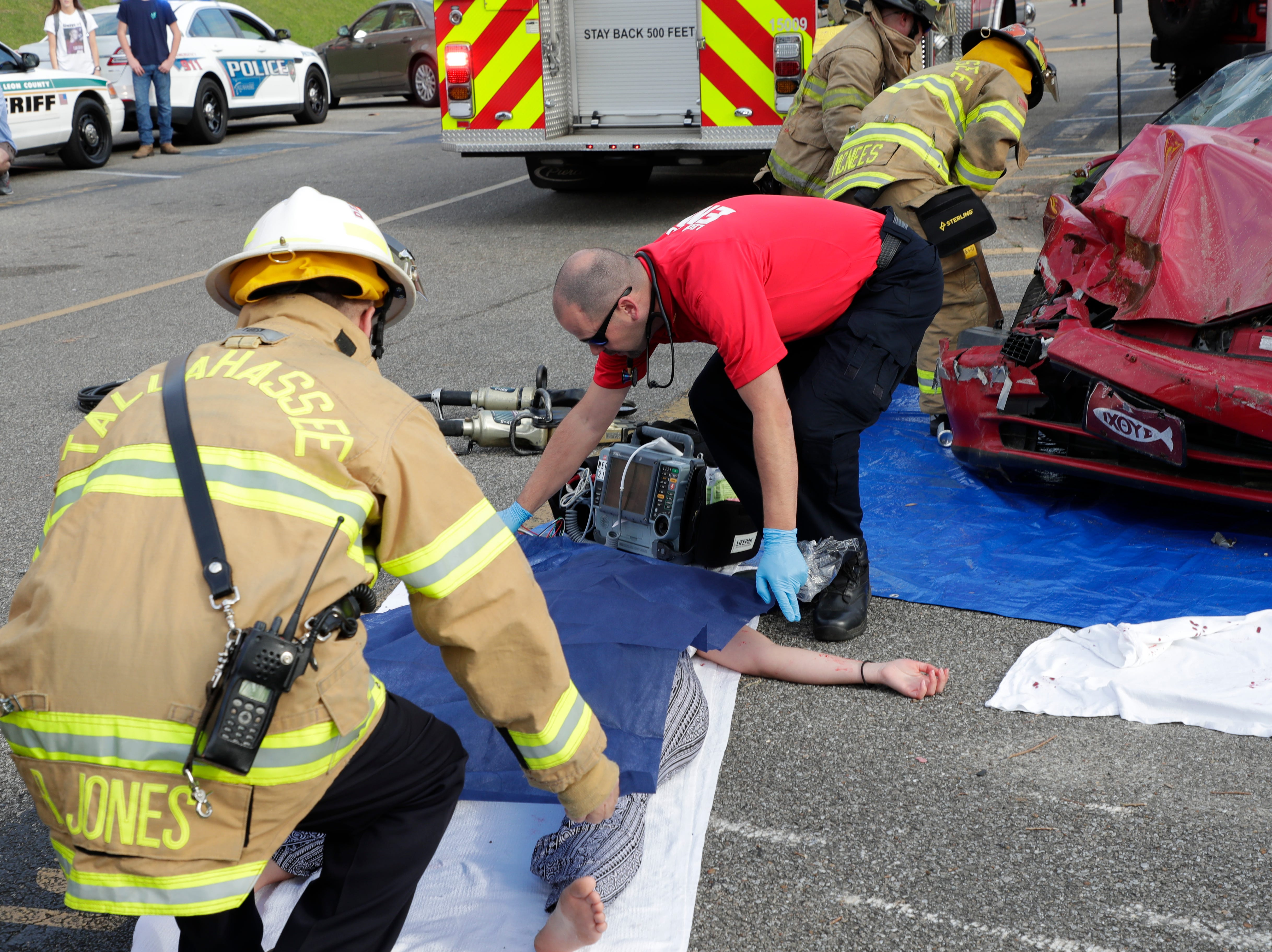 A Leon County firefighter and Leon County EMS paramedic drape a tarp over Christina Huettel as she portrays being killed in a drinking and driving accident. Leon High School partners with the county safety officials to give a simulation on the consequences of drunk driving before the students leave for spring break Friday, March 15, 2019.