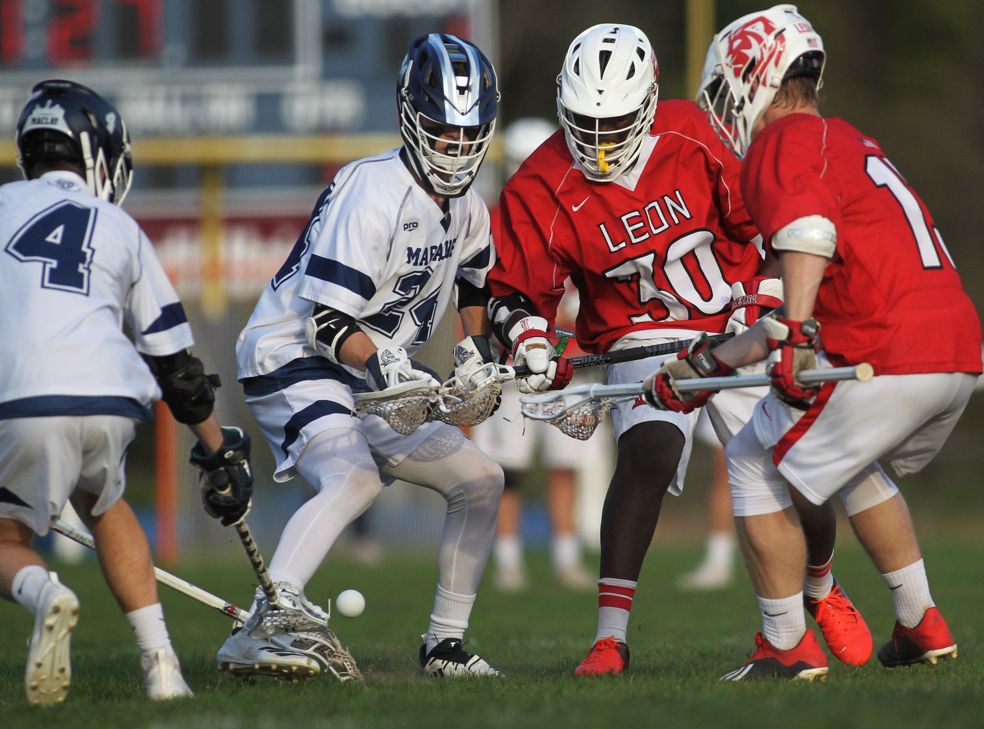 Maclay's Stone Foster (4) and Liam McAbee (24) fight for possession of a loose ball against Leon's Maurico Hyde (30) and Casey Palmer (13) as the Marauders' lacrosse team beat Leon 15-5 on their annual Military Appreciation Night on March 12, 2019.