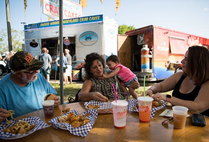 "Joanna Wortham (center), visiting from Georgia, holds her granddaughter, 9-month-old Callia Faleris, while eating alongside husband David Wortham (left) and daughter Autumn Faleris, of Grand Valkaria, at the ShrimpFest & Craft Brew Hullabaloo on Friday, March 15, 2019, at Riverview Park in Sebastian. ""I usually go to the beach,"" Joanna Wortham said, adding that it was her first time at the festival. ""She loves people,"" she added, referring to her granddaughter."