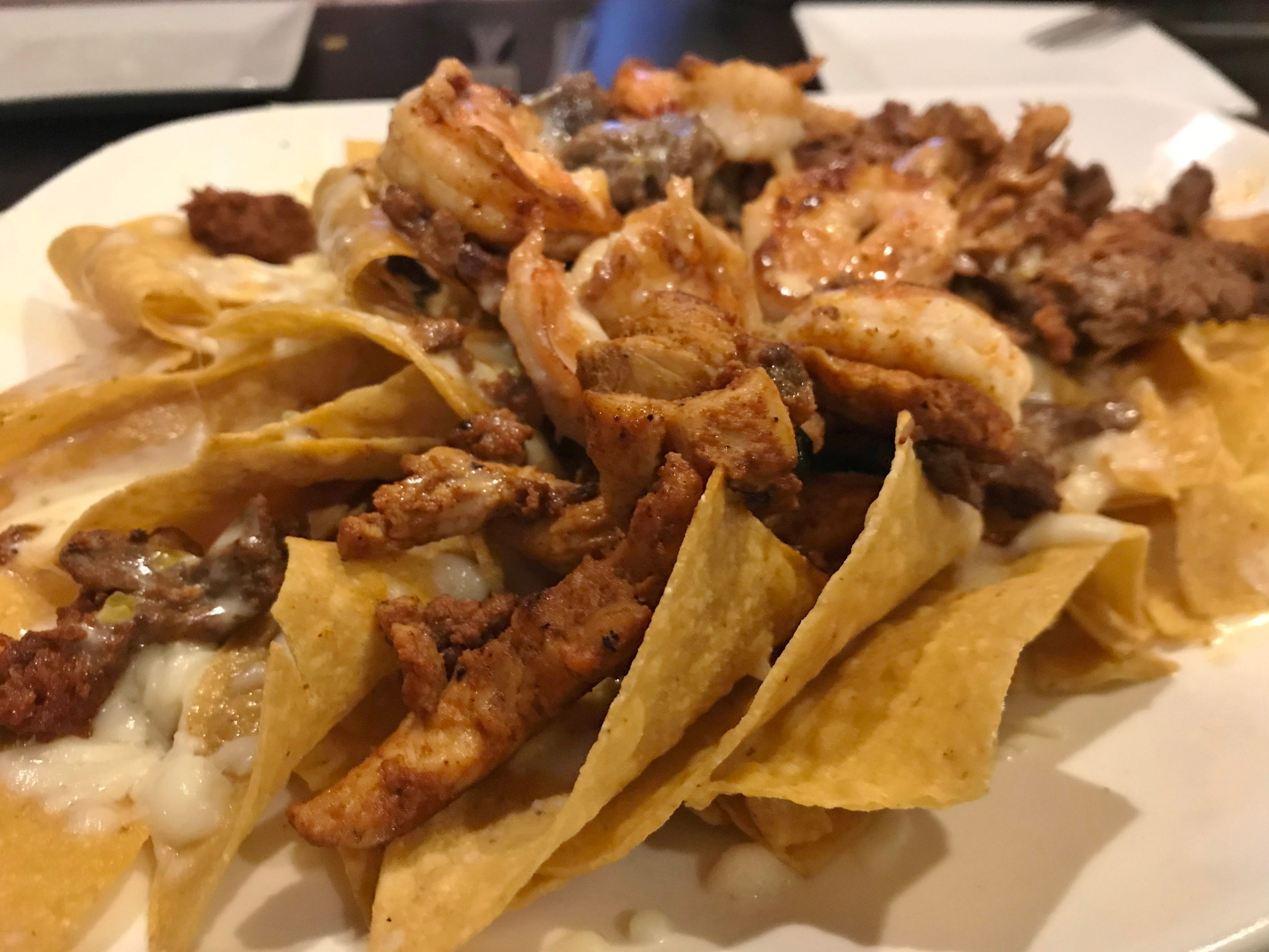 Casa Amigos Nachos were covered with shredded cheese, queso, grilled chicken, steak, chorizo, and shrimp.