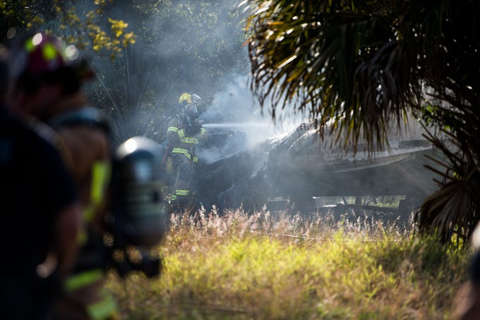 """Indian River County Fire Rescue personnel work at the scene where a boat exploded and caught fire Friday, March 15, 2019, on a lot adjacent a home on Manly Avenue in Sebastian. Nobody was hurt in the incident, which was """"suspicious,"""" Indian River County fire officials said."""