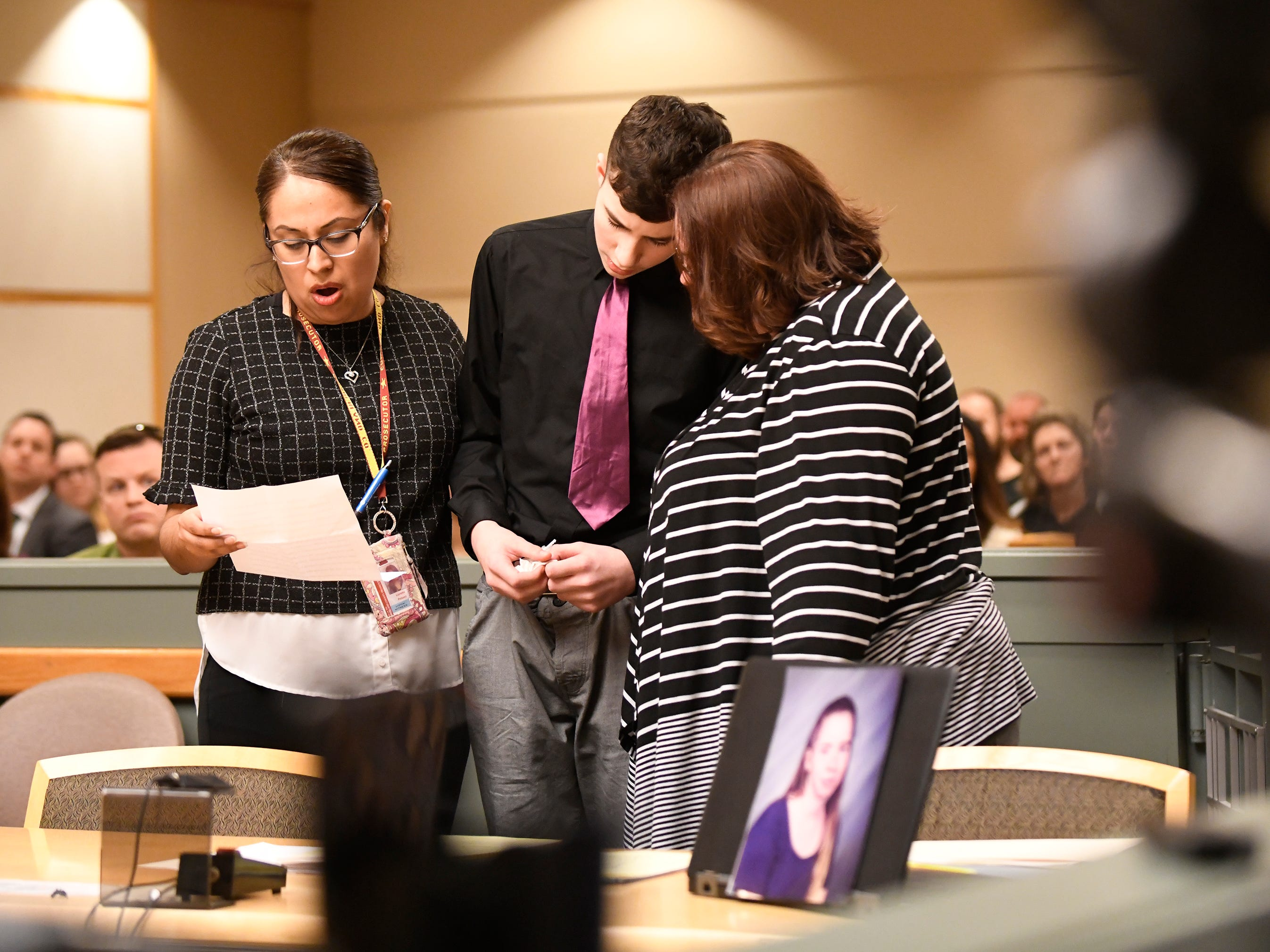 Director of Victim-Witness Advocacy Lorena Palaez reads a letter written by Jeremiah E. Monell's son. The son, who is named for his father, is flanked by Palaez, left, and his aunt, Thelma Monell, right, in Cumberland County Superior Court on Friday, Mar. 15, 2019. Monell, who stabbed and slashed his estranged wife to death, was sentenced to spend the rest of his life in a state prison.