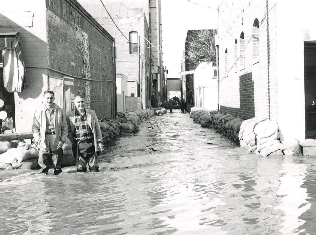 In this photo from the December 1955 flood, two men pose for a photo amid swirling floodwaters.