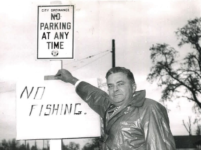 """In this photo from the December 1955 flood, a man posts a """"no fishing"""" sign to a post."""