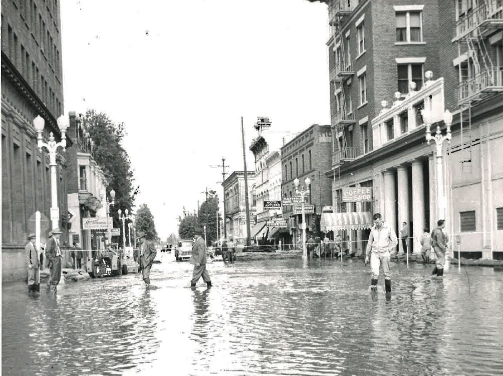 In this photo from the December 1955 flood, sightseers pass through the Central Business District.