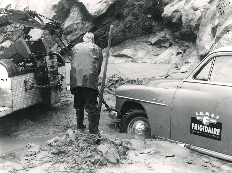 In this photo from the December 1955 flood, a man works to free car stuck in a deep channel that cut through Highway 198.