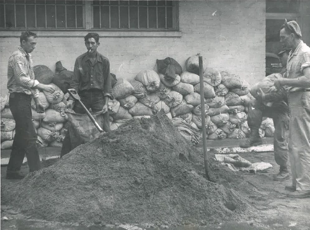 In this photo from the December 1955 flood, men work to fill sandbags.
