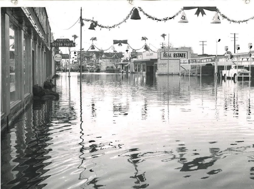 In this photo from the December 1955 flood, three feet of water reflect yule decorations on East Main Street.