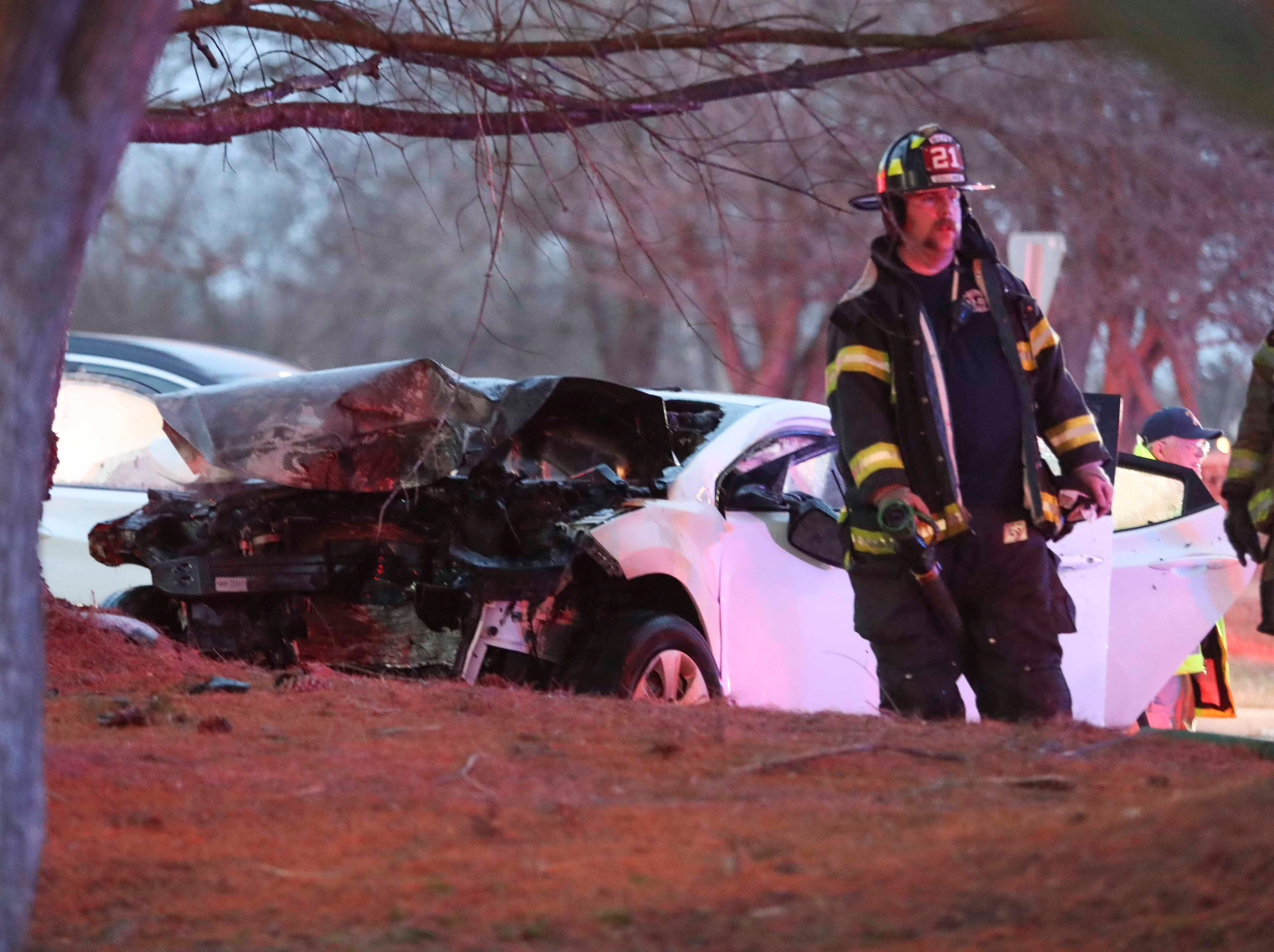 Firefighters work after extinguishing a fire in a car involved in an accident on Kirkwood Highway in Milltown early Thursday evening. Bystanders said the driver was rescued from the car as the fire started to break out and was transported to an area hospital with serious injuries.