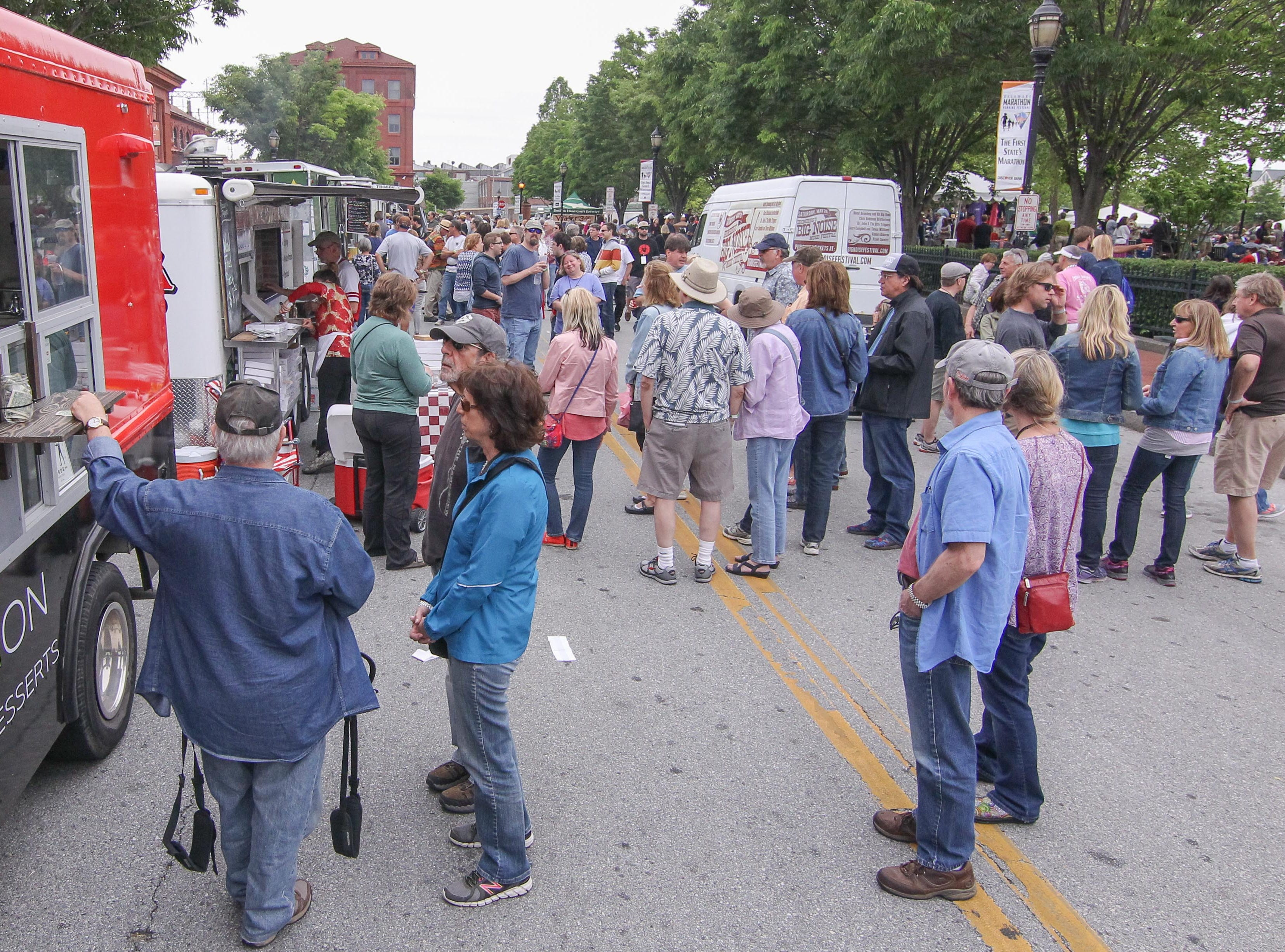 Crowds of people gather at food trucks in between set during Bromberg's Big Noise Music in 2017 at Tubman Garrett Park in Wilmington.