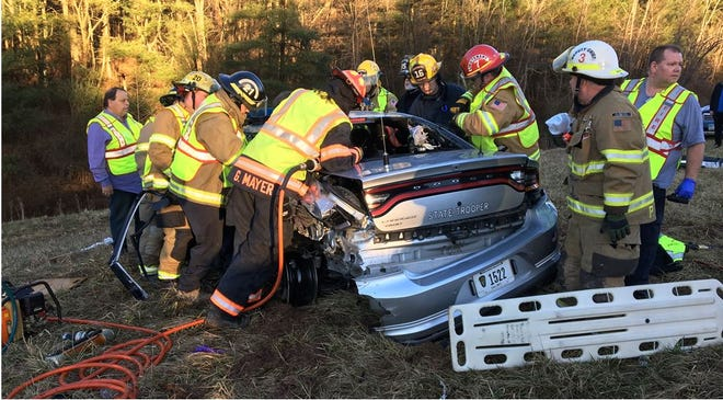 Emergency crews work to free Eric Knowlton from his Highway Patrol cruiser after it was badly damaged by a passing tractor-trailer.