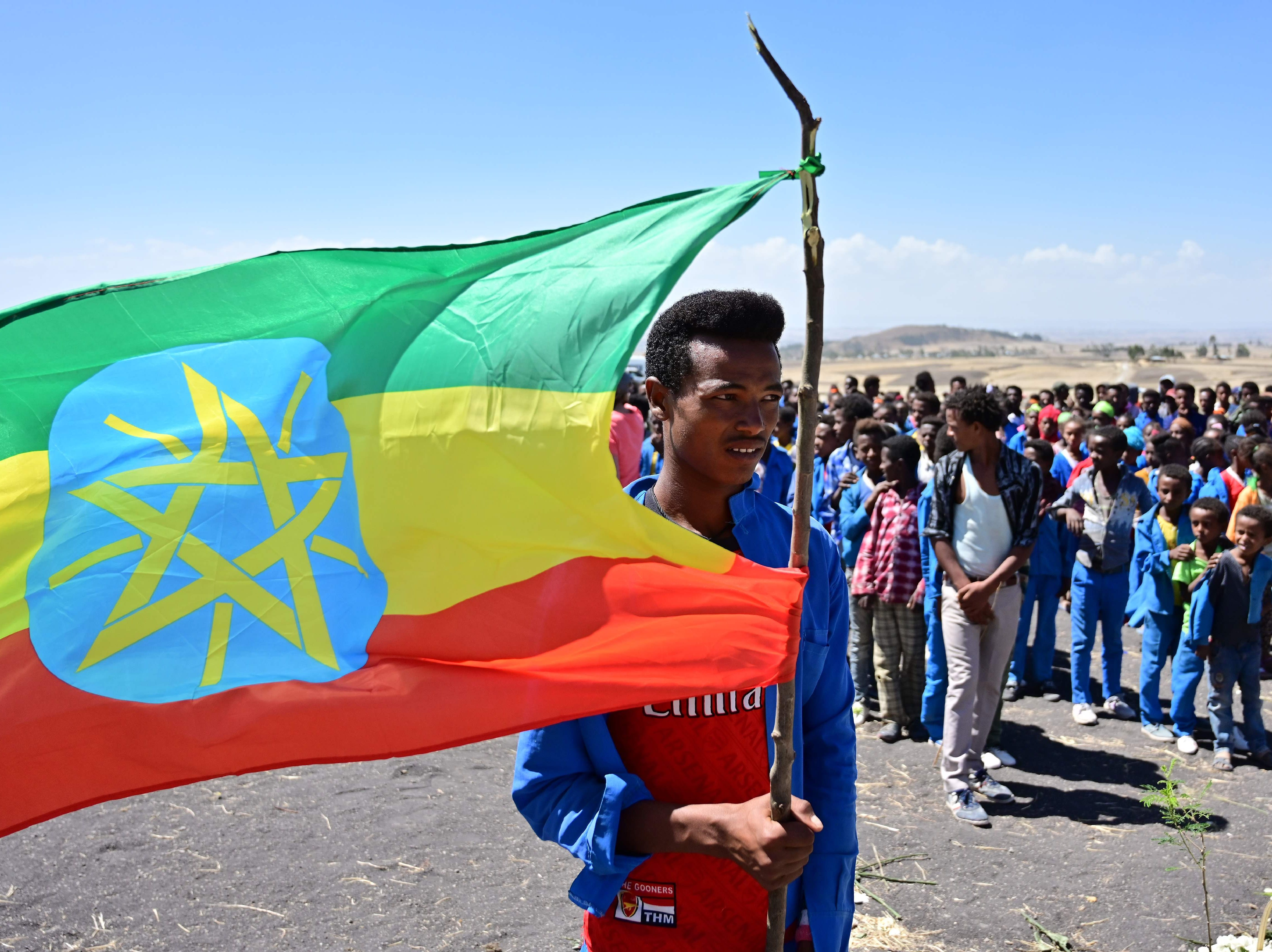 A man holds an Ethiopian flag as children from neighboring Hama elementary school arrive to pay condolences at the  crash site of the Ethiopian Airlines 737 MAX aircraft.