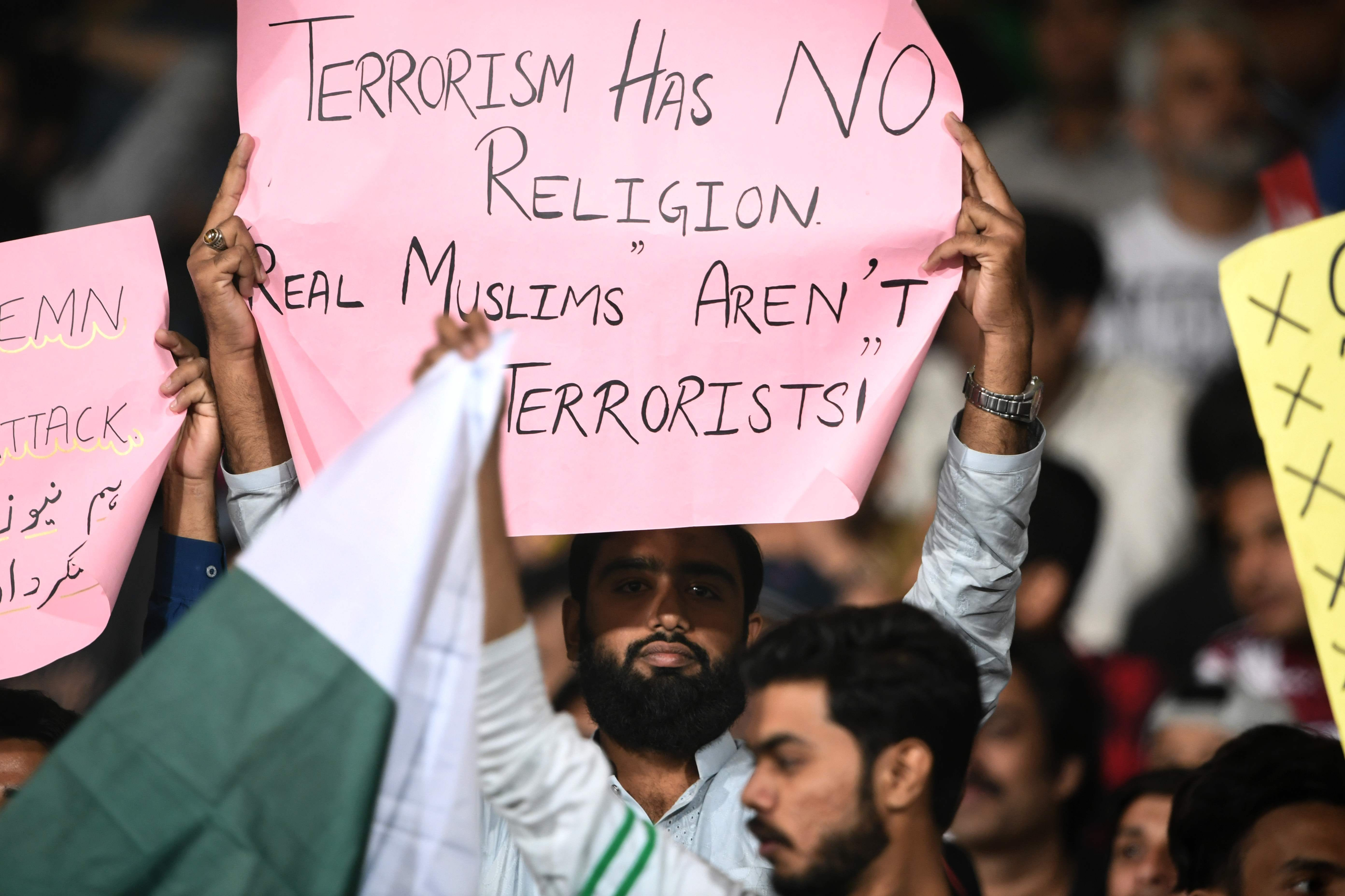 "A cricket supporter holds a sign reading ""Terrorism has no religion real Muslims aren't terrorists!"", after the mass shooting that occurred in New Zealand, during the 2nd elimination PSL Twenty20 match between Peshawar Zalmi and Islamabad United in Karachi on March 15, 2019."