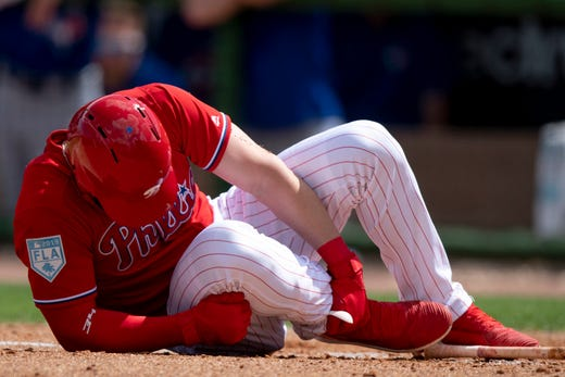 March 15: Philadelphia Phillies outfielder Bryce Harper grabs his foot after being hit by a pitch during the sixth inning against the Toronto Blue Jays.
