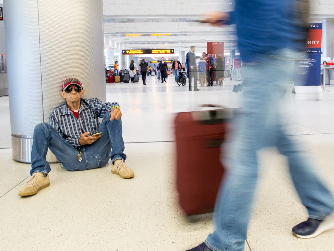A man takes a break in the busy Terminal J at Miami International Airport on Feb. 23, 2019.