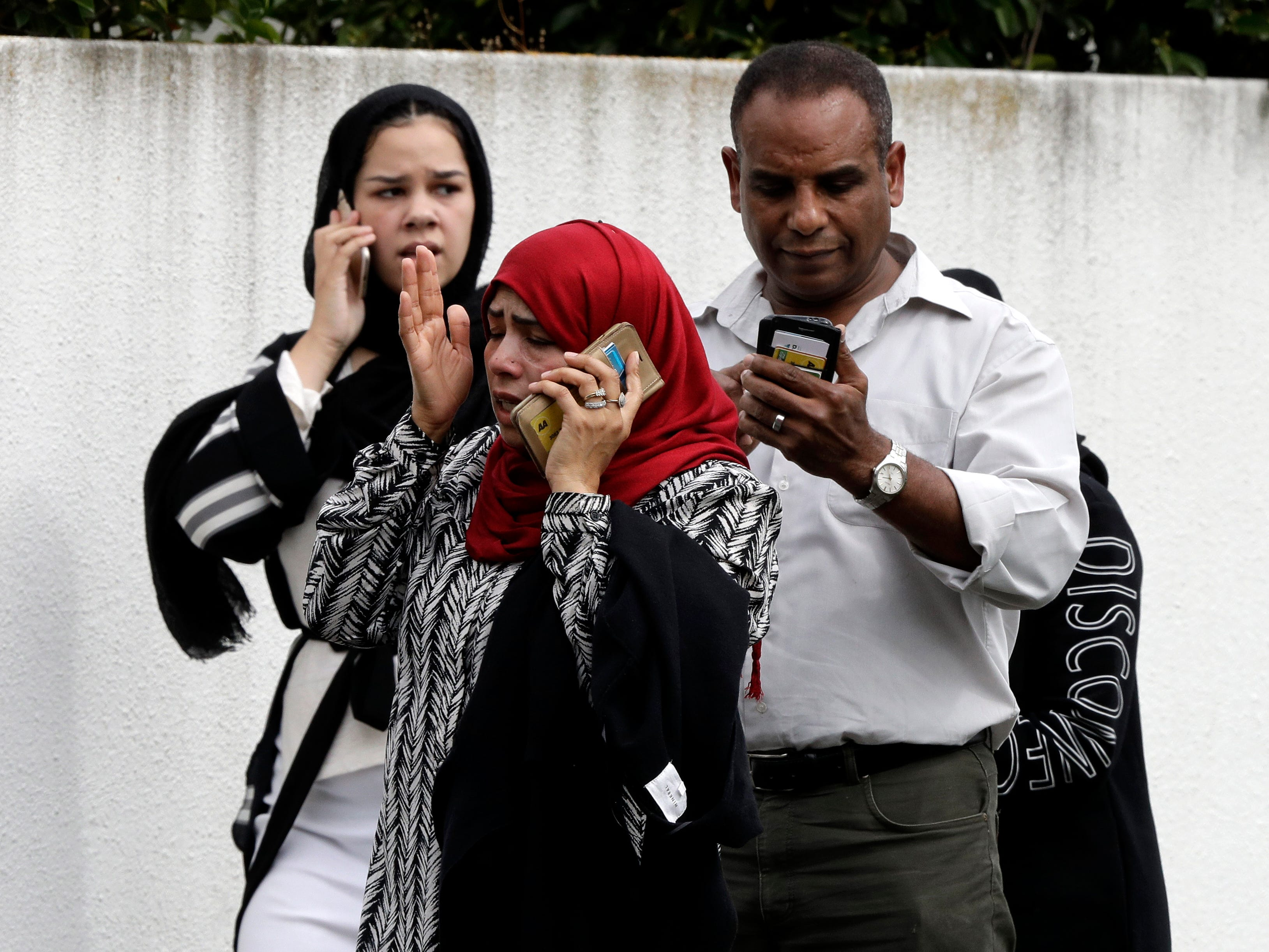 People wait outside a mosque in central Christchurch, New Zealand. At least 49 people were killed and more than 20 were seriously wounded in the shootings at two mosques in Christchurch.