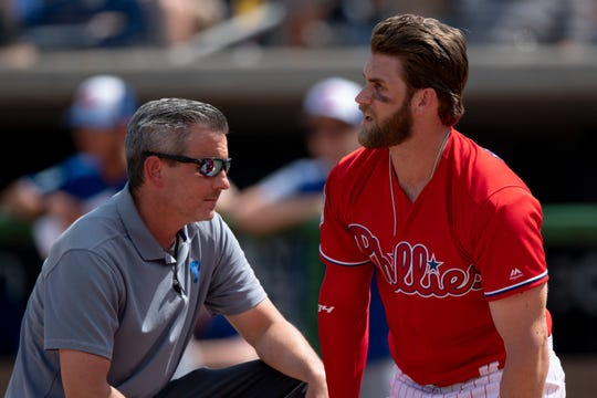 Philadelphia Phillies outfielder Bryce Harper is checked on by a trainer after being hit by a pitch during the sixth inning against the Toronto Blue Jays.