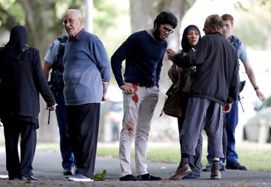 People stand across the road from a mosque in central Christchurch, New Zealand. After the reported shootings, local authorities warned people in central Christchurch to stay indoors.