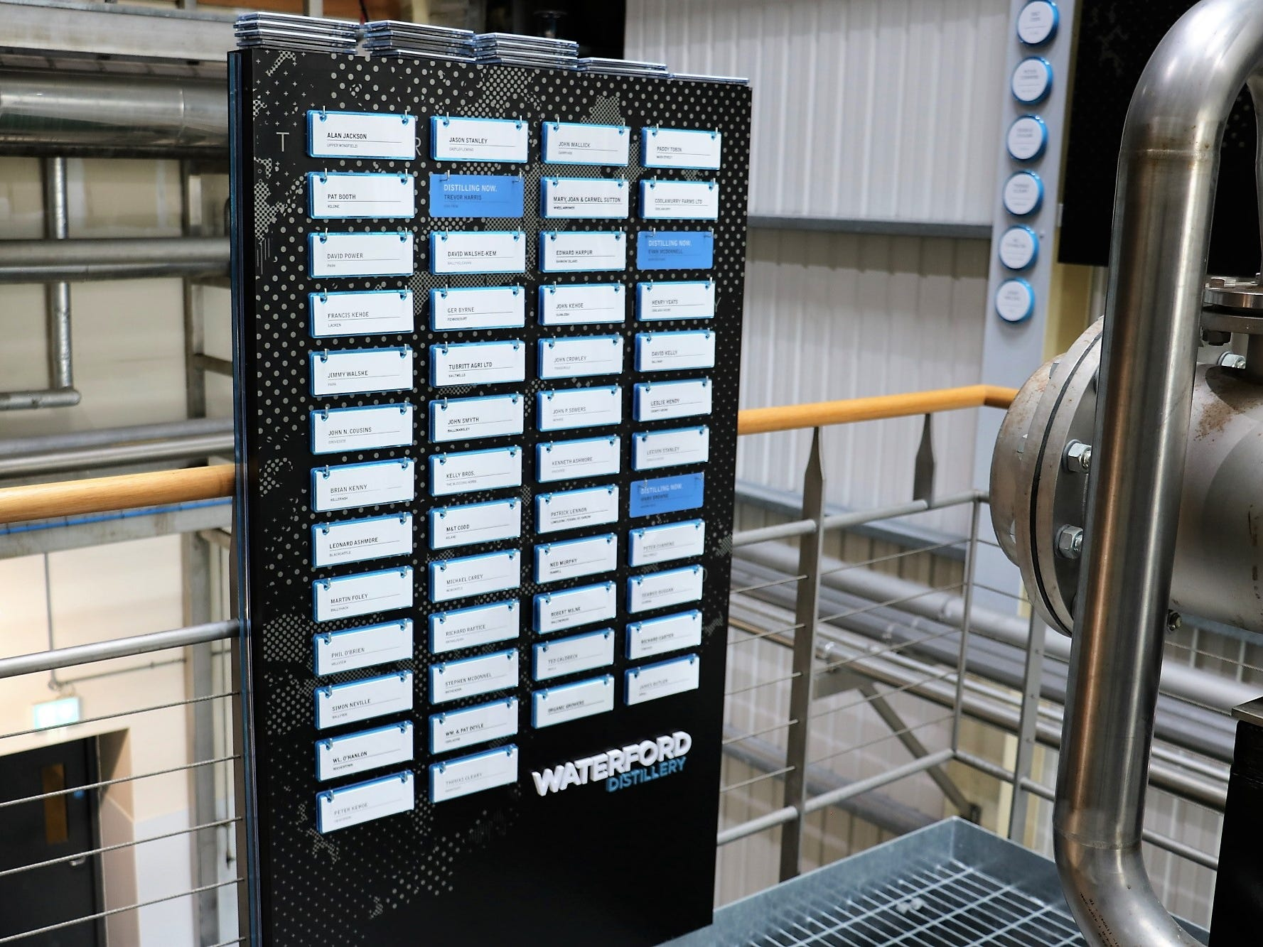 """Next to the wall-hanging is a list of farmers, and the name tags which get moved to the spirits safe display when in use. """"Every week is another farmer, and we do about 40 per year,"""" says Mark Newton, the distillery's head of communication."""
