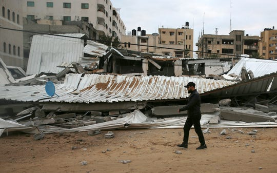 A Palestinian inspects the damage of destroyed building belongs to Hamas ministry of prisoners hit by Israeli airstrikes in Gaza City, early Friday, March 15, 2019. Israeli warplanes attacked militant targets in the southern Gaza Strip early Friday in response to a rare rocket attack on the Israeli city of Tel Aviv, as the sides appeared to be hurtling toward a new round of violence.