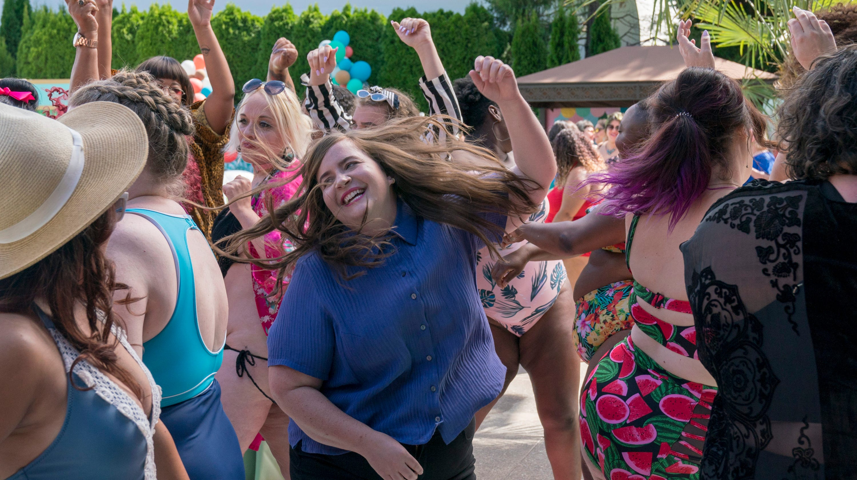Aidy Bryant in Shrill. Annie at the pool party in the same blue blouse, this time she is dancing full-out among the crowd of party-goers in swimsuits and sun hats. She has a huge smile and her hair is tossing around, her arms waving.
