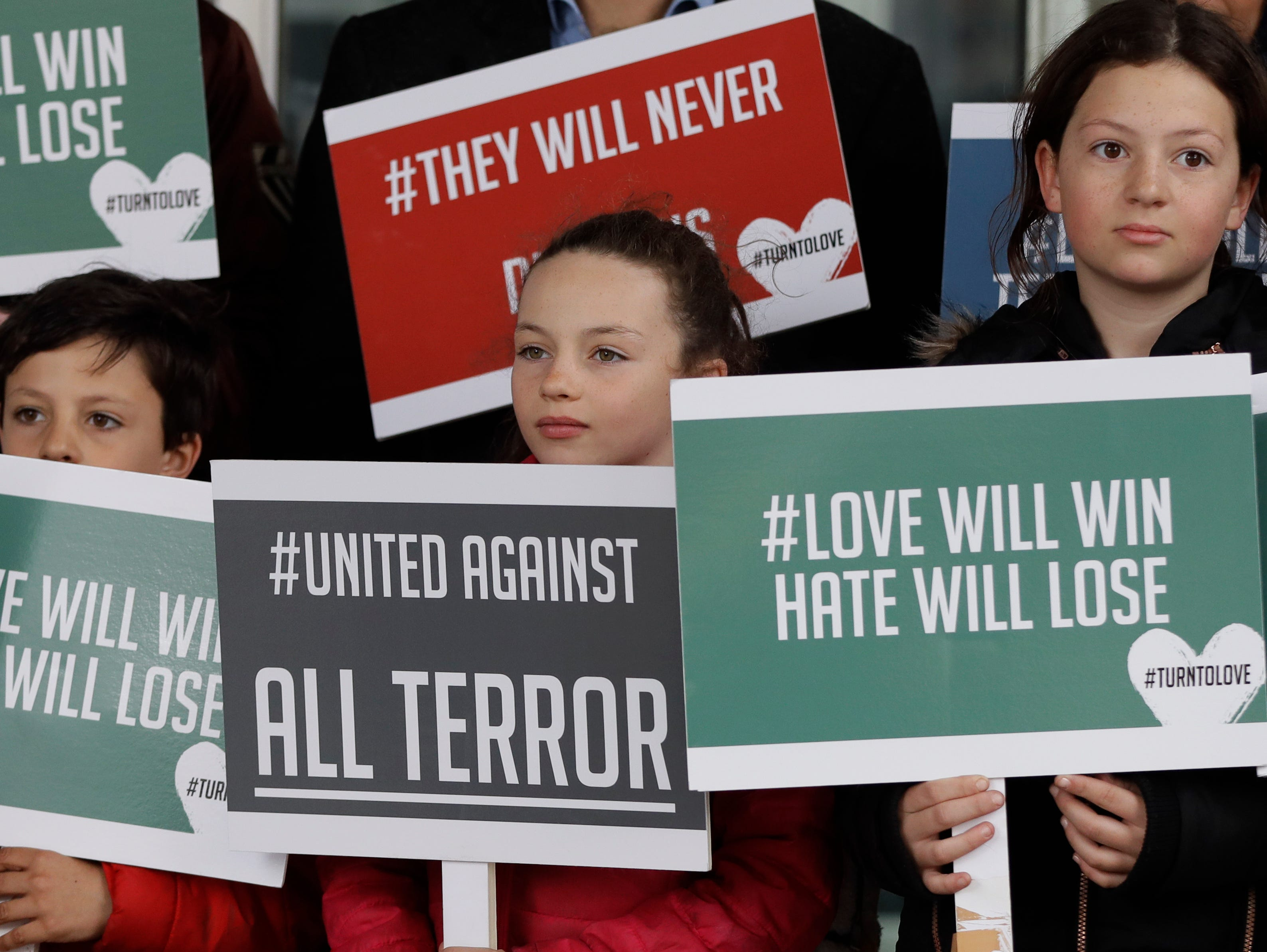 Young demonstrators hold banners from multi-faith group 'Turn to Love' during a vigil at New Zealand House in London, Friday, March 15, 2019.