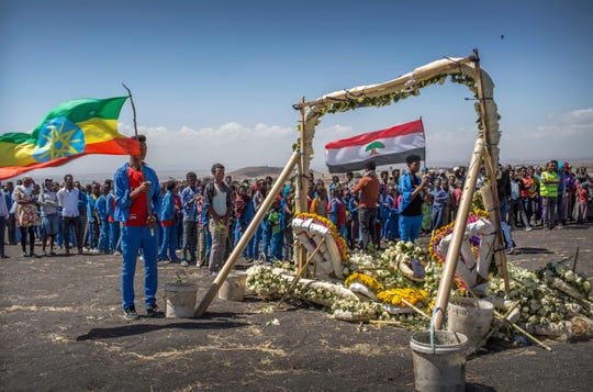 Students from Hama elementary school, who walked an hour and a half from their school in the surrounding area to pay their respects, stand next to floral tributes at the scene where the Ethiopian Airlines Boeing 737 Max 8 crashed shortly after takeoff on Sunday killing all 157 on board.