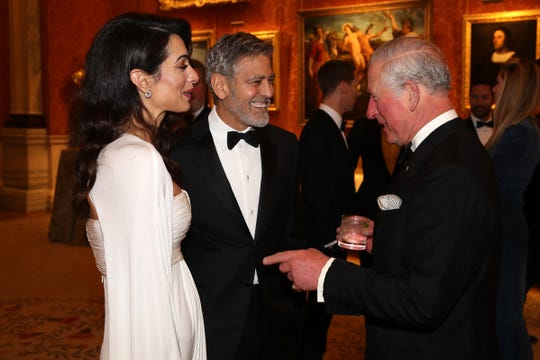 Amal and George Clooney speak with Prince Charles at a dinner to celebrate The Prince's Trust, hosted by Prince Charles at Buckingham Palace on March 12, 2019.