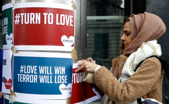 A demonstrator hangs banners from multi-faith group 'Turn to Love' during a vigil at New Zealand House in London, Friday, March 15, 2019.