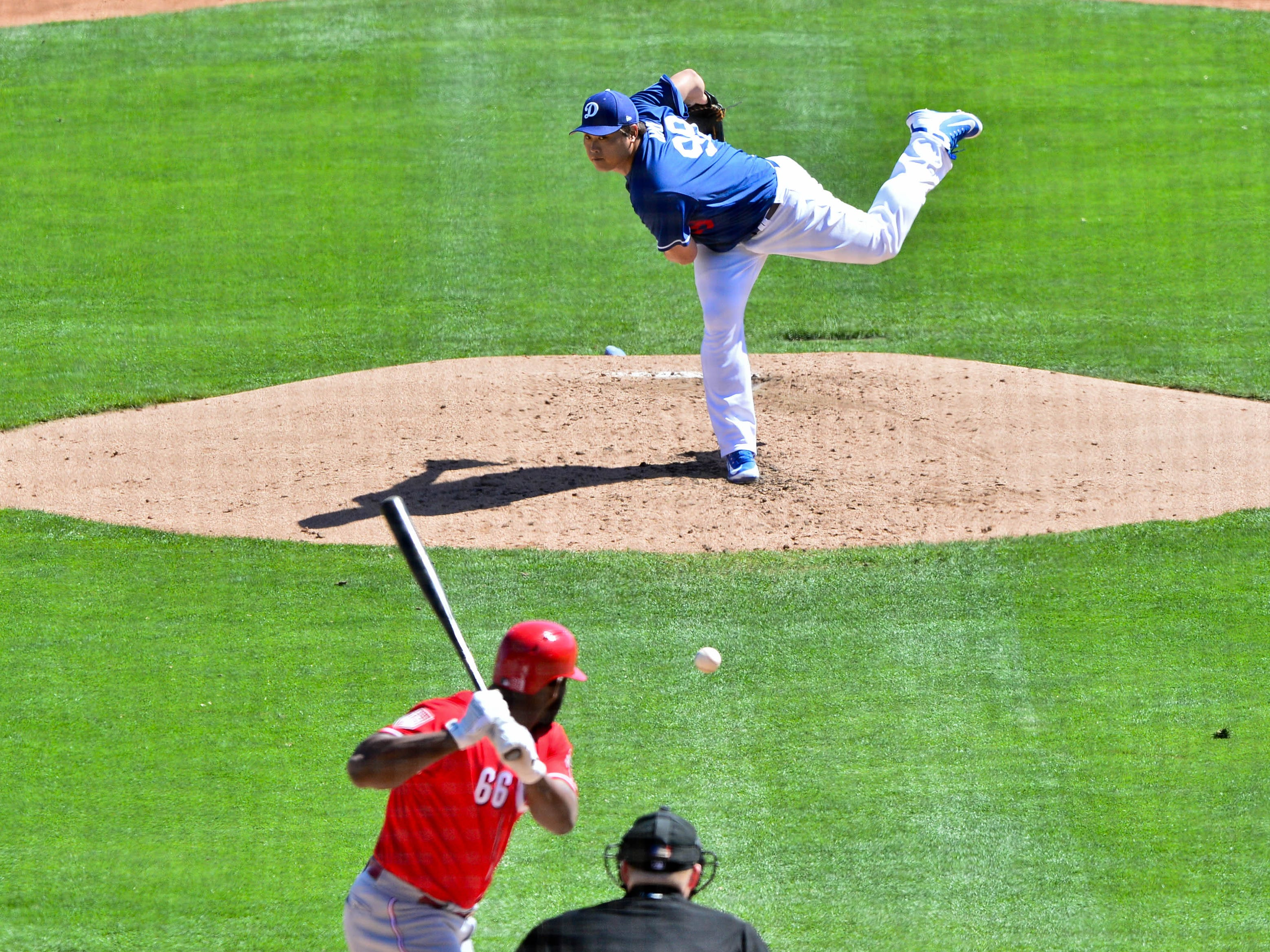 March 14: Los Angeles Dodgers starting pitcher Hyun-Jin Ryu throws to the Cincinnati Reds' Yasiel Puig during the third inning at Camelback Ranch.