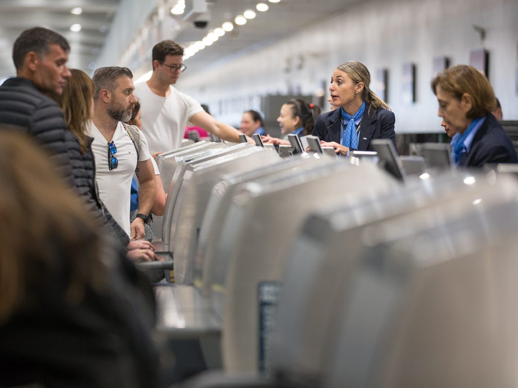 Airline staff check in passengers for their flights at Miami International Airport on Feb. 23, 2019.
