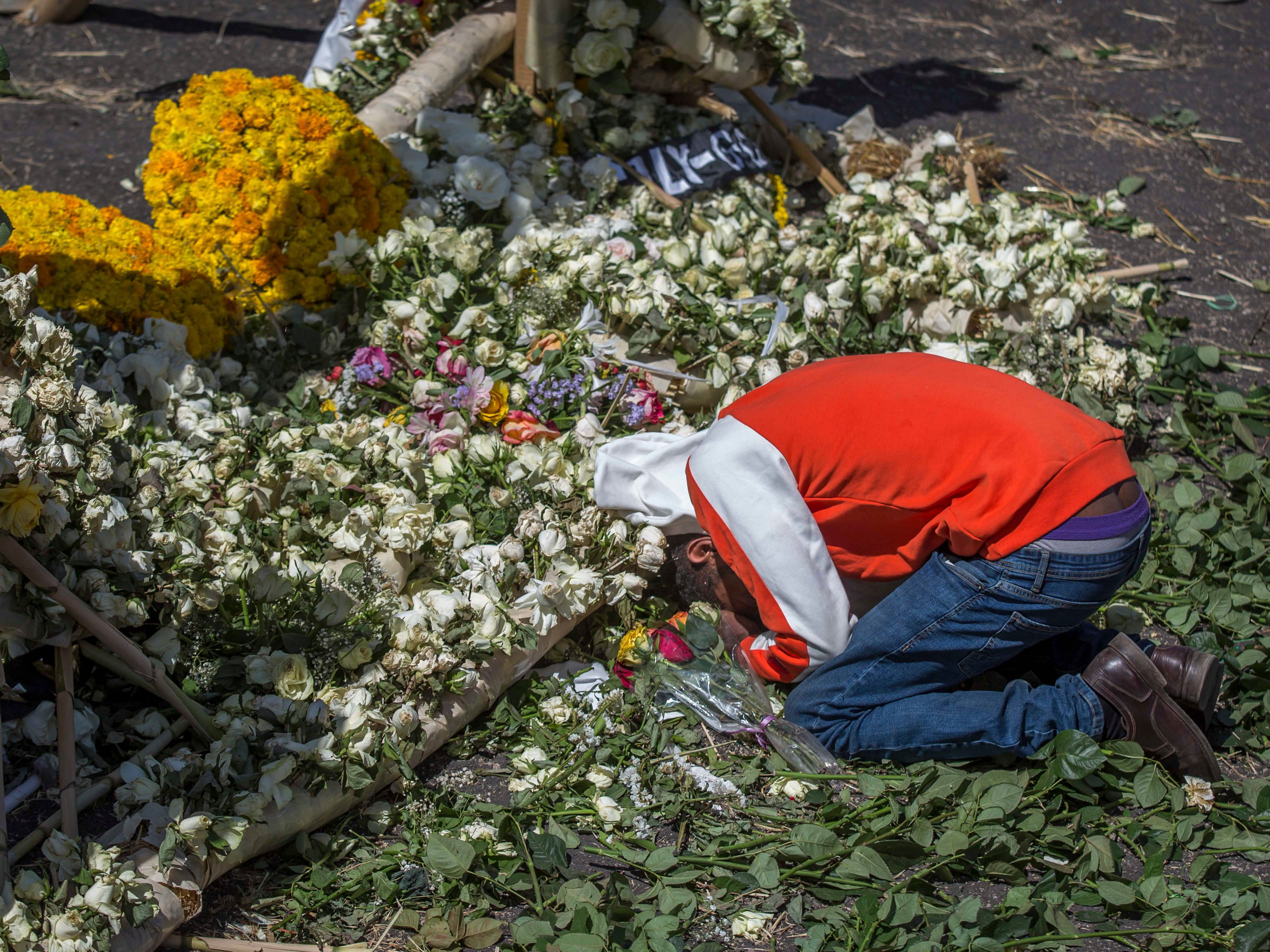 An Ethiopian relative of a crash victim mourns and grieves next to a floral tribute at the scene where the Ethiopian Airlines Boeing 737 Max 8 crashed shortly after takeoff on Sunday killing all 157 on board, near Bishoftu, south-east of Addis Ababa, in Ethiopia Friday, March 15, 2019. Analysis of the flight recorders has begun in France, the airline said Friday, while in Ethiopia officials started taking DNA samples from victims' family members to assist in identifying remains.